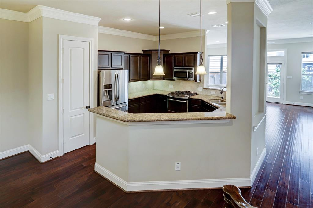 On the first floor of this home flanked by the dining and family rooms, is a spacious open kitchen with stainless steel appliances, including a wine/beverage fridge. There is also coveted pantry space (the door to the left of the refrigerator).