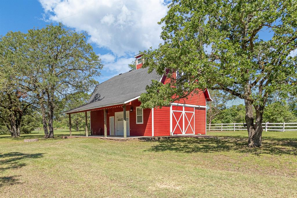 10 acres of beautiful Texas countryside just waiting for your ranching dreams! This property offers a unique combination of mature trees and open pastures with stunning views, exactly right for a weekend getaway or full-time homestead. Fully fenced. The beautiful red barn dominium includes 1120 sf of shop with a half bath downstairs and 800 sf upstairs offering a large living space with kitchen and full bathroom. Step outside to find a 35x35 pole barn with tack room, orchard with 20 trees and watering system, one-acre pond to fish that includes an aerator, luscious trees situated around the property and several acres already cleared awaiting your vision. There is a 3-bedroom, 2-bathroom mobile home built in 1983 on the property, that will be sold as-is. Live in there while you finish out your dream! Rhino and riding lawn mower negotiable, pool table and couch included. Both city water and septic on site, well water serves orchard and corral. Bring your horses today and make this yours!