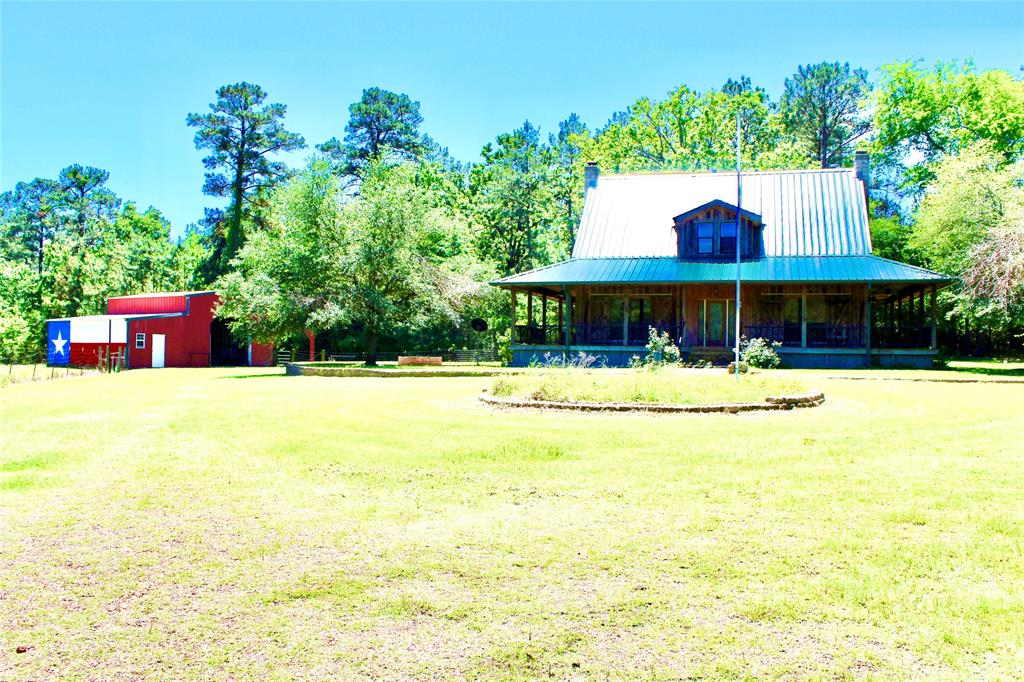 RUSTIC CHARM!   Nestled on 3.650-acres, this farmhouse sits beautifully just off the county road. This two-story, four bedroom, three bathroom home has plenty of room for entertainment. It comes with a large bunkroom upstairs, along with three guest rooms. Downstairs, you will enjoy the open floor plan with master bedroom and large living area. The living area is outfitted with a stone wood-burning fireplace. The kitchen has beautiful finishing's and granite countertops. The master bedroom is complete with a stone wood-burning fireplace. Outside, you will love the wraparound porch, as well as the covered carport in the back with built-in barbecue pits. The property also comes complete with two large storage barns and a small pond. For your private showing, give us a call today.
