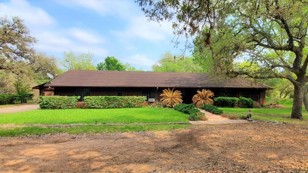 This is a rare listing and won't last long at this price! Right at 42 acres of beautiful oak trees with a large brick home situated in the back so you have the privacy you are looking for. Because there is a creek as one border of the property you have bountiful wildlife! The home is in the flood zone but has had a berm engineered by the corps of engineers around it to protect it from floodwaters. The home is a custom-built home with many custom features including custom cabinets with 2 pantries, and double ovens. The round fireplace in the center of the huge living space has 2 openings for wood-burning fires and one stove. The 2 car garage has a storage room with a full bath and a sauna! There are cattle pens with a barn with a cement floor and lean to. There is an additional 1800sf barn with 2/3 cement floor and 3 stalls. Seller owns minerals and is offering 20% to the buyer with an acceptable offer. Schedule your tour now to see this fabulous place!