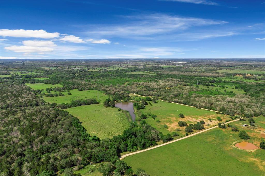 246 sprawling acres in North Gonzales county available! The property comes equipped with a main house, a barn, storage shed, multiple horse stables, 3 ponds, a seasonal creek, as well as cattle! Located an hour and a half from Houston, 45 minutes from Austin or San Antonio, 424 CR 437 is tucked right in between I-10 to the south and HWY90 to the north. The east side lot boundary line is CR 437 which has complete road frontage along it, making it ideal to subdivide. The property is essentially 2 side by side contiguous tracts with about 50% wooded (varietal hardwoods - post oaks, pines, mature live oaks) and 50% grazing pastures. You can access the back of the property from the main house or use CR 437 which has multiple access gates. Fish, hunt, hike, explore, entertain clients; the uses for this prime piece of Texas land are endless!