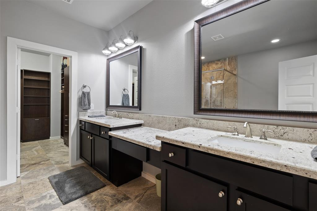 The luxurious primary bath feature dual vanities with modern finishes.