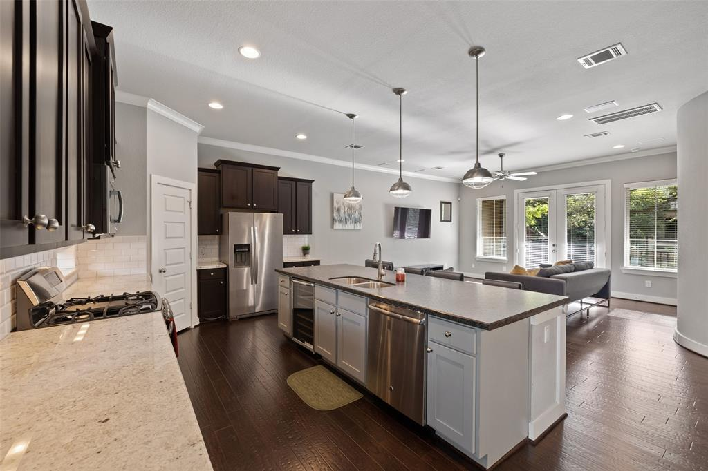 The open floor plan features wood floors, crown molding and lots of natural light.