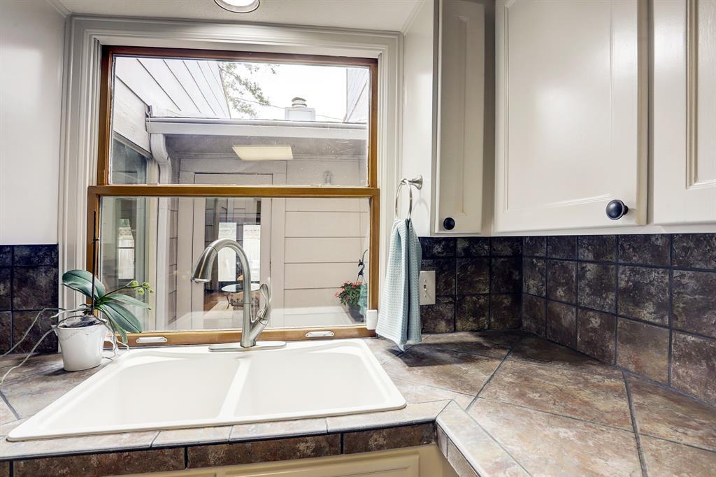 Kitchen window overlooks naturally lit atrium.