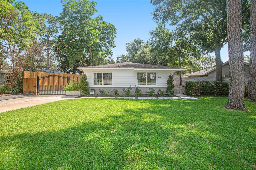 """Stunning updated 1 story home in desirable Garden Oaks. On a large lot surrounded by mature trees across from a small pocket park. Interior features original distressed hardwood floors throughout which gives the home a warm cozy feel. Seller opened kitchen 2019 removed wall between the kitchen and living area for a modern design, installed island with custom """"butcher block"""" top with pull out drawers and extra storage, custom oak cabinets, white quartz countertops, farm sink, enclosed laundry area with custom built-ins, surround sound in living, kitchen, dining area. Master updated with Carrera marble countertops, frameless glass shower with rain shower system & handheld showerhead. 2nd bath updated. The large outdoor patio provides great entertainment space with automatic landscaping lights, outdoor speakers, sprinkler system. Double wide driveway with Auto-driveway gate provides extra parking leads to detached 1 car detached garage. 2020 Privacy fence installed."""
