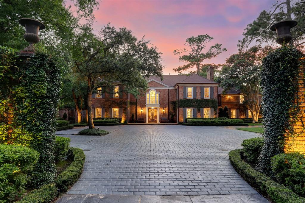 At the end of a private drive lies a sprawling River Oaks mansion, complete with a myriad of amenities. The front elevation features Georgian architectural touches, such as symmetrical chimneys and ornate crown molding on the interior. The 6 bed, 6.5 bath home includes a four-car garage, resort-sized pool and spa, pool house, and a covered balcony. The kitchen is blanketed in honed marble, complete with Wolf and Sub Zero appliances. The two-level primary suite includes a completely marble bathroom and a staircase leading to the fashion palace overhead. High ceilings and hardwoods abound throughout the interior. Outside you will find freshly-manicured grounds, including a lush, sunken garden right off the dining room. This home is the quintessence of modern tradition.