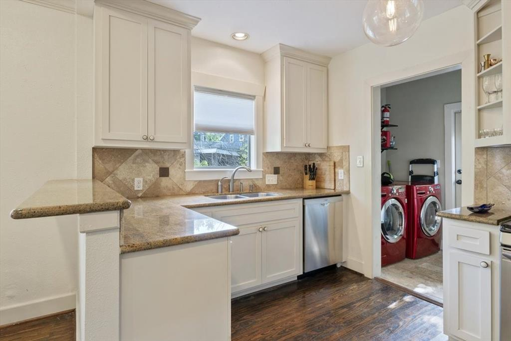 Granite counters and large cabinets help appoint this well-lit kitchen.