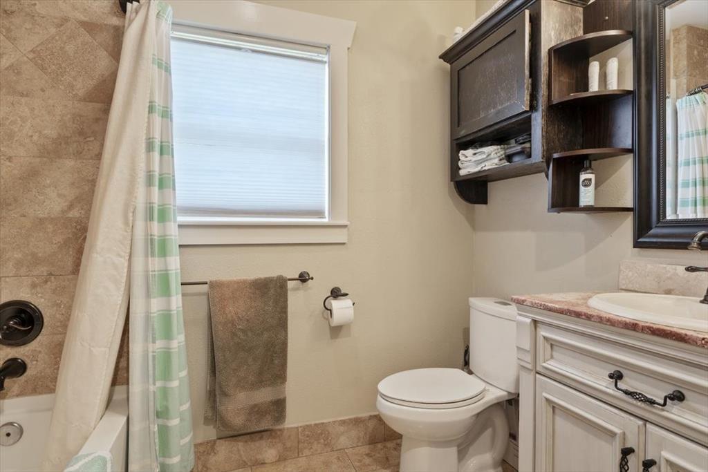 Roomy bathroom with stone floors and elegant vanity.