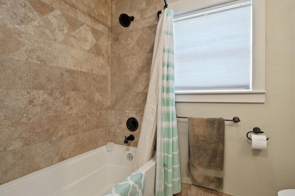 Roomy bathroom with shower/tub combo, stone floors and elegant vanity.