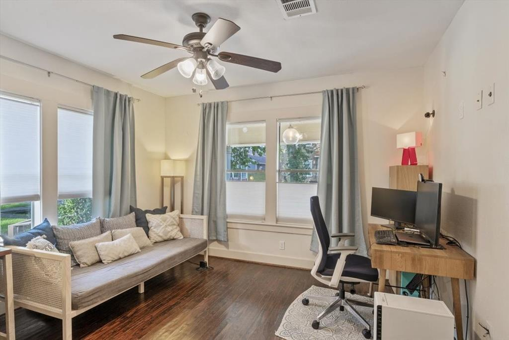 A lovely bedroom kept cool with a ceiling fan has a useful closet and multiple windows.