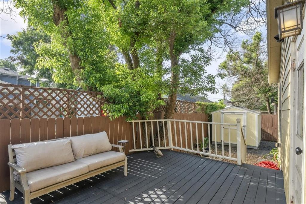 The tree-shaded back deck leads down to the side yard, storage shed and driveway.
