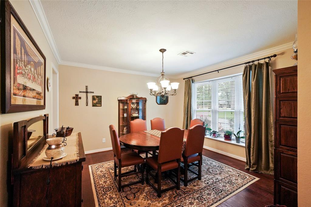 This formal dinging room includes crown molding, a chandelier, and updated wood floors.