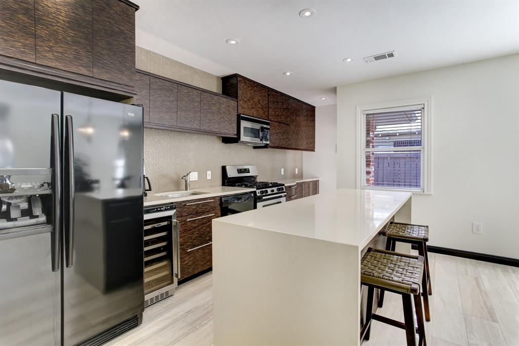 In addition to the side-by-side refrigerator there is a wine/beverage fridge.  Hidden just to the left of and around the corner from the window is the door to the driveway, converted garage and back yard.