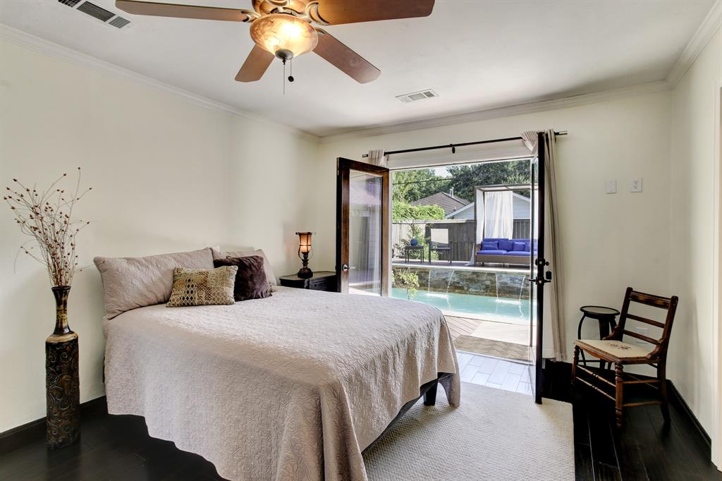 The spacious primary suite sits in a back corner of the home overlooking the waterfall pool and back yard.