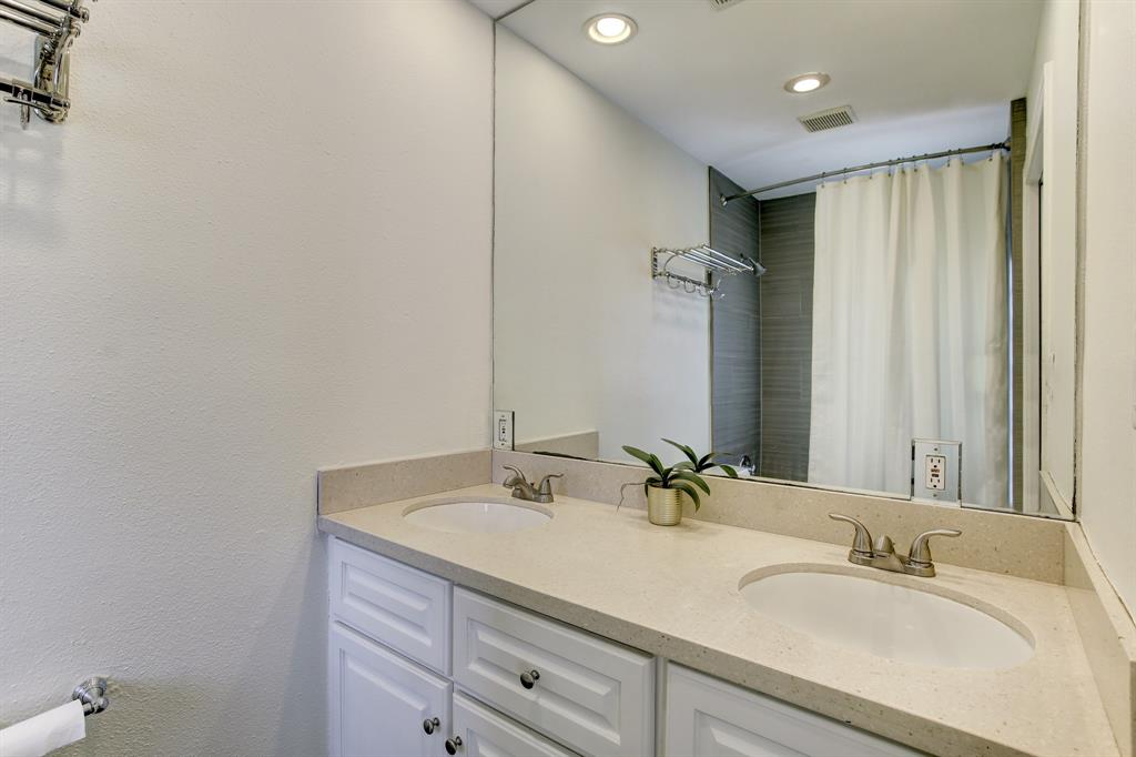 The primary bath has a double sink vanity as well as a shower/tub combo with a glass block window.  There is excellent natural light in this bathroom.