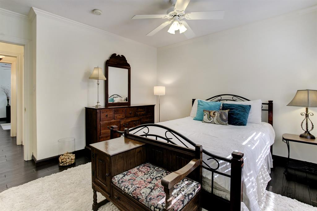 Down the hall from the primary suite is the first of two additional bedrooms.  This one is comfortably set up with a queen bed and additional furniture pieces.