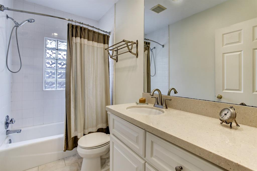 The second full bath at the back of the home also has a shower/tub combo with a privacy glass block window.