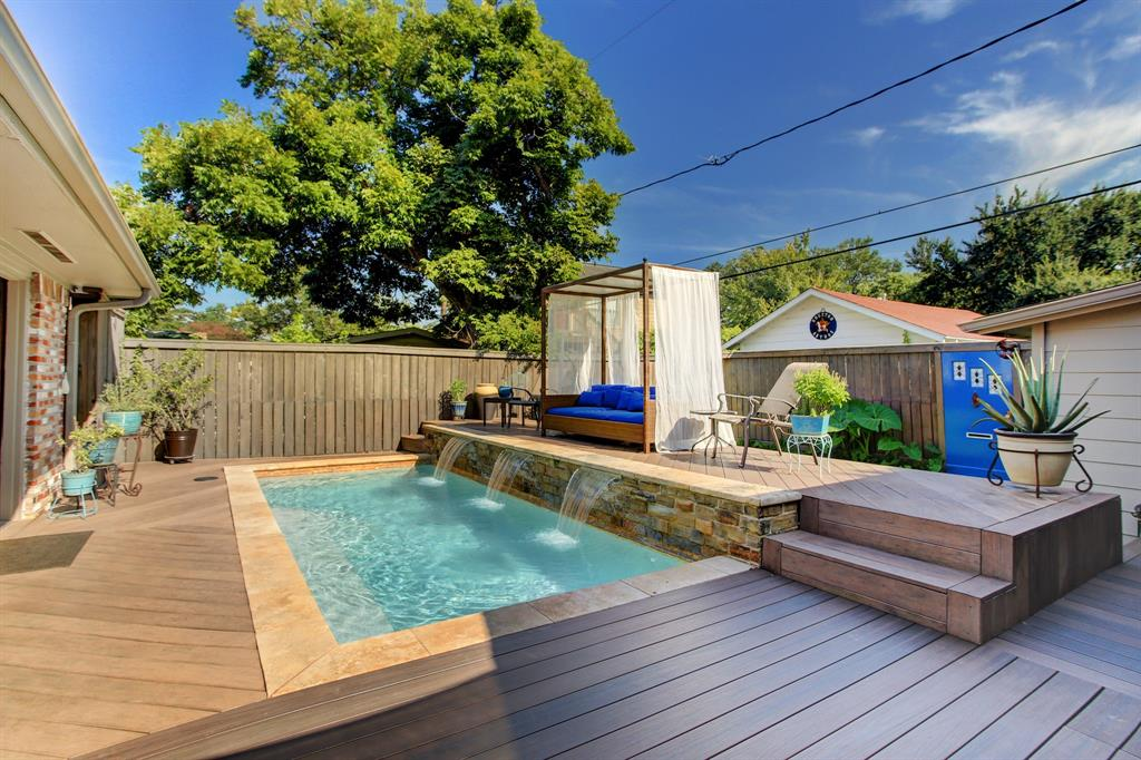 The back yard is an absolute oasis! The plunge pool with waterfall feature has a heater and is surrounded by deck space.