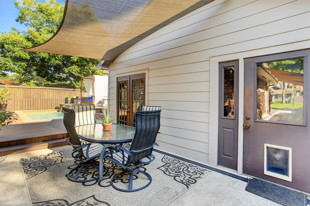 In addition to all the deck space surrounding the pool, a concrete patio outside the converted garage is a shaded area for outdoor dining (driveway and patio sails will stay).  Note the doggie door, perfect for a pup to access the air conditioned space and also have the run of the fully fenced back yard.