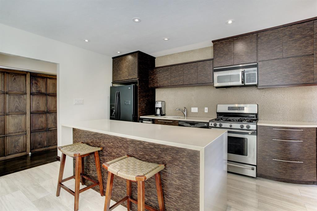 The kitchen with quartz counters includes an island breakfast bar and light tile floors.