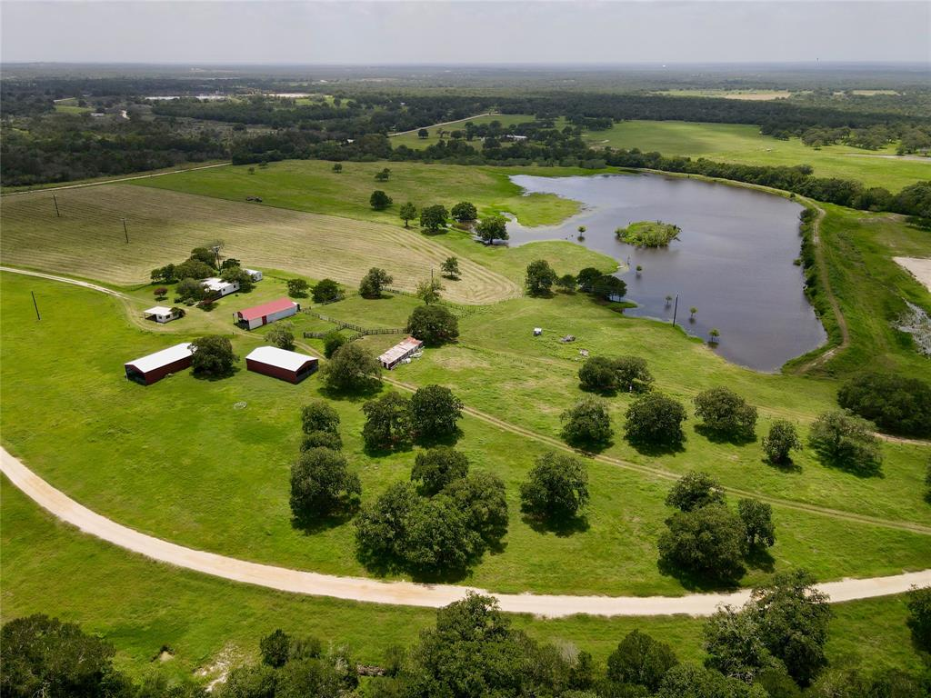 Beautiful, well maintained ranch, just west of Old Moulton in eastern Gonzales County! The 5 acre lake is full of 5-10lb blue catfish that swim right up to the bank at feeding time! The lake is stocked with blue cats, channel cats, crappie, and bass! The owner has planted Cypress trees in the water for structure and habitat for the fish and waterfowl. The property is dotted with mature live oaks, post oaks, and pecans with some century oaks lining the creeks on each side of the property. The property is income producing with a hay and cattle lease in place. The ranch is perfect for agricultural production with improved grasses for horses or cattle. The creeks and draws provide perfect habitat for wildlife including deer, turkey, and wild hogs. The cabin is perfect for the weekend stays. There is also an outdoor man-cave with a kitchen and bath, laundry room; perfect for hosting BBQ's and parties. Three 30x60 barns. Come take a look at this ranch on a quiet county road!