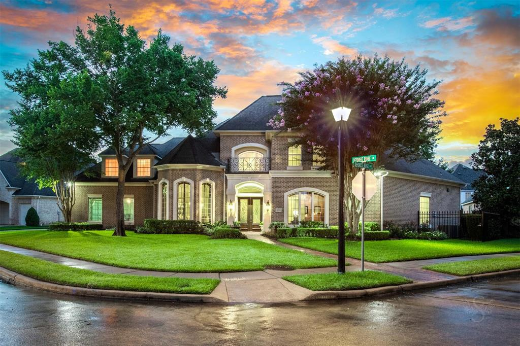 """Meticulous true custom brick in gated, award winning Cinco Ranch offering NEW ROOF AUGUST 2021, warm block paneled study + formal living that could be used as 2nd study, 2 fireplaces, primary suite w sep sitting area & professionally updated spa-like bath featuring Grohe faucets, soaking tub, huge walk-in shower & giant his/hers closets, extensive millwork & builtin cabinetry thruout, quality plantation shutters, generous 2ndary bedrms, light & bright island kit w Thermador 5 burner gas cktop, dbl ovens, recent 48"""" builtin refrigerator & microwave + tons of counter space & cabinetry w pullouts, butlers pantry, huge utility, an oversized 3 car wide, side entry garage w workshop area, prof epoxy flooring & Tesla charger. Updated ac's, fencing, landscaping including 7 trees, water softener, chandeliers, wood & natural stone floors. Add cov patio & balcony off gamerm overlooking nearly 1/2 acre culdesac lot to allow your dream pool w plenty of yard to spare. NEVER FLOODED NO FROZEN PIPES!"""