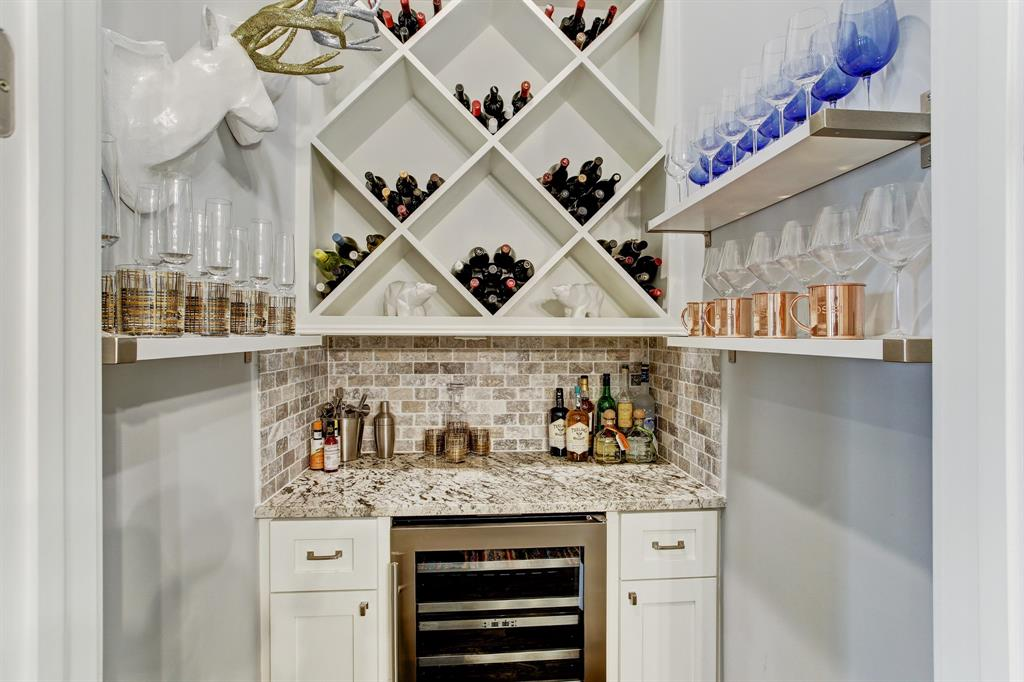 This fabulous walk-in dry bar includes a wine/beverage refrigerator as well as copious amounts of storage space for the mixologist or sommelier in the house. French doors close it off when not in use.