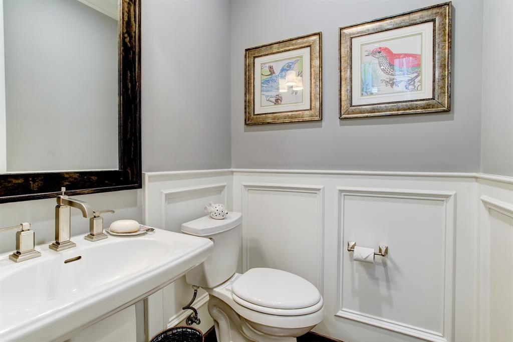 Tucked on the landing to the second floor is a half bath thoughtfully located out of the living space. The custom mill work in this home extends throughout.