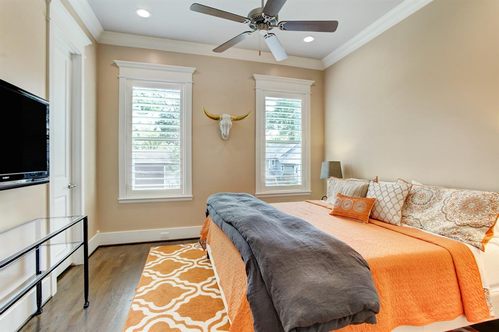 The first of two guest bedrooms is quite large, this is a king bed with nightstands on each side. As well the walk-in closet (door to the left) is unusually large offering great additional storage space. This bedroom looks over the back yard.