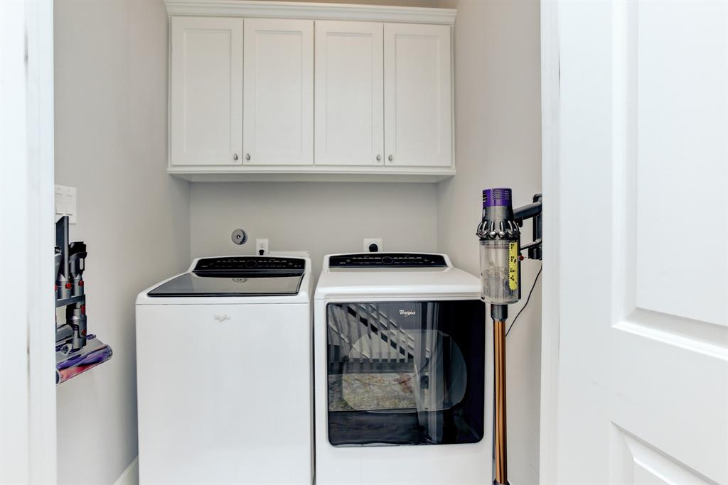 The laundry area has space for various cleaning equipment as well as cupboard space for supplies.