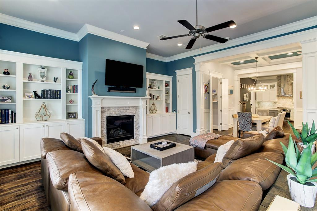 The living room on the first floor is unusually spacious, and accommodates substantial and comfortable furniture pieces. Note the custom built-ins on either side of the fireplace.