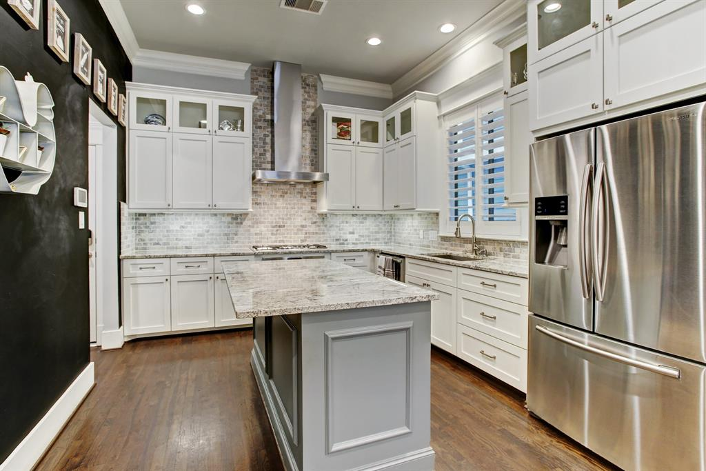 The chef's kitchen includes a center island, great counter and cabinet space, and a range hood over the gas stove. The doorway to the left toward the back of this photo leads to the garage door and a pantry.
