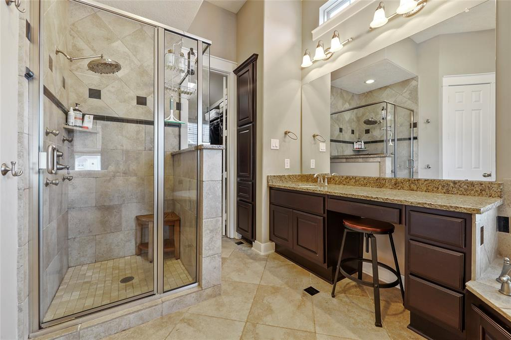 The luxurious primary bath features dual vanities (one not pictured) with modern finishes.