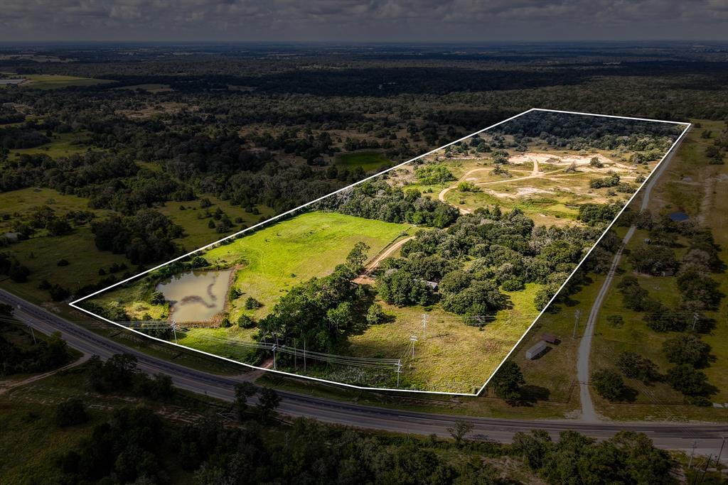 50.45 Acres of multi-use land just 7 miles southwest of Caldwell. Property features access of paved, FM 908 Rd with approx. 730' of road frontage. Enter through 40+ year old, mature Pine Tree driveway to privacy and seclusion. Open pasture with stock pond and small, 720 sq. ft. hunting cabin. Exterior siding and roof replaced in 2018, freshly painted exterior. Single-story on concrete slab. Bluebonnet Electric and Deanville Water Supply. Cross over the wet-weather creek to the middle of the property to the open area and existing sand pit. Beyond the sand excavation area is approx. 15 acres of heavy woods with an abundance of wildlife. Continue to make this property a recreational haven, or build your custom home overlooking the pond. Continue to sell sand for income production or turn that area into a huge lake! Lots of options and possibilities for this tract of land. AG. EXEMPT, NO restrictions, NO zoning NO floodplain! Partial perimeter fencing only 2-3 years old.