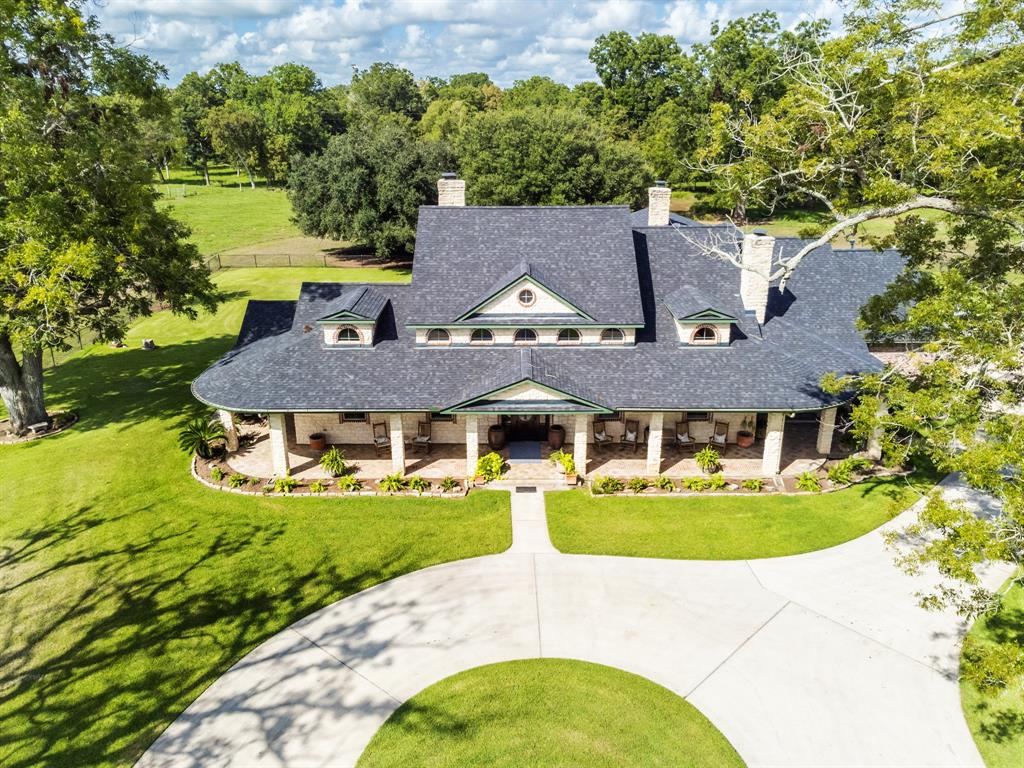Welcome to this beautiful country oasis in the heart of much desired Fulshear. 10 plus acres surround this unbelievable 4100 square foot home.  The wrap around stone and tile porch welcomes you as you walk to the front door. The decour of the home is elegant yet inviting with a feel of Texas country. Soaring ceilings will delight as you walk into a bit of heaven in the family room featuring wood floors, a 2 story stone fireplace and bead board ceiling. Huge formal dining room is surrounded in windows and accentuated with a 2 sided stone fireplace. Fireplace also opens to breakfast area and gourmet kitchen boasting granite counters, Viking 6 burner gas stove, 2 dishwashers and unbelievable cabinet storage. Beautiful master suite also includes a stone fireplace and French doors leading to the front patio. Home has a total of 4 fireplaces! Back covered patio includes dining spaces and outdoor kitchen. Beautiful mature trees enhance the property along with a stocked pond.  Breathtaking