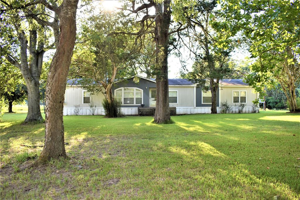 If you are looking for a slice of country with easy access to I-45 look no further! This open concept well maintained manufactured home is located in the highly sought after town of Centerville. The house is absolutely precious with elegant features through out it. This home features 2 large living areas, a wood burning fireplace, a huge kitchen with a nice island that is open to the dining room and living room. The master bedroom has  his and hers closets and the over sized master bathroom offers double sinks, a garden sunk, jetted bathtub, separate shower and walk in closet. Once you walk out the French doors to the covered back porch you have a peaceful view of pure blissful country life. There are open pastures with large trees and the enormous yard offers plenty of shade for those hot Texas days. One of the best features of this land are the LARGE trees that are scattered through out the property. Bring your cows, horses, dogs and family as this place will not last long!