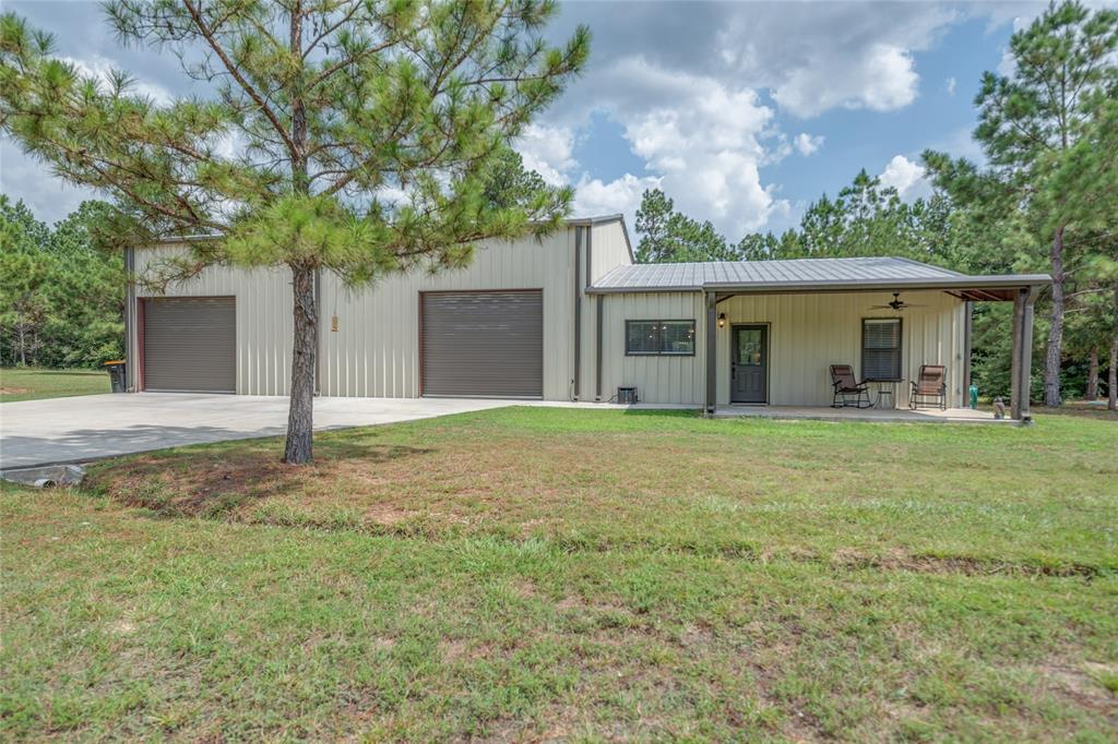 2 bed, 1.5 bath barndominium with 40'x50' INSULATED SHOP on 5.19 ACRES located in Timber Line Estates! The interior features crown molding, tile floors throughout with carpet in the bedrooms, recessed lighting and access to the shop. The kitchen features a large breakfast bar, an island, stainless appliances and looks into the living and dining rooms. The primary bedroom is spacious with a double door closet and easy access to the full bath. The secondary bedroom is just off of the dining room. The full bath features a double sink vanity, shower/tub combo and a large linen closet. The shop has 3 roll up doors for easy access, a 12 ft. Big Ass Fan, and a 12'x30' lean to with electrical hookup for RV. The property is partially fenced with a natural barrier at the back for privacy. 24'x24' steel carport with concrete pad. NO HOA, septic system and electrical large enough for additional 3,000 sq. ft. house.