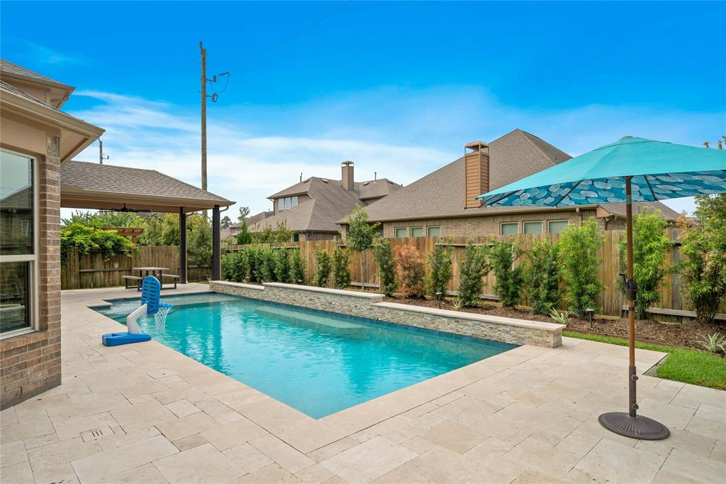 Check out this gorgeous two-story home just listed in the highly sought after neighborhood of Harmony! This home is nestled in the manned gated section of Harmony Creek, which is in walking distance to the neighborhood amenities. This beautiful home features a 17,563 gallon gunite pool with a tanning ledge, a heater/chiller, and custom travertine decking around the pool. The outdoor covered patio was also extended with beautiful wooden vaulted ceilings and 2 bluetooth controlled fans. At the time the pool was built, there was a half bathroom built outside for guests while using the pool, as well as, an outdoor shower to rinse off under. The home also has a 24kw Generac generator that powers the entire home, including the pool. Make sure to check out the custom video of the neighborhood amenities in the attached video link tour. Harmony offers many amenities to its residents: 2 pools, basketball and tennis courts, 2 splash pads, walking trails, gym, community center and numerous parks!