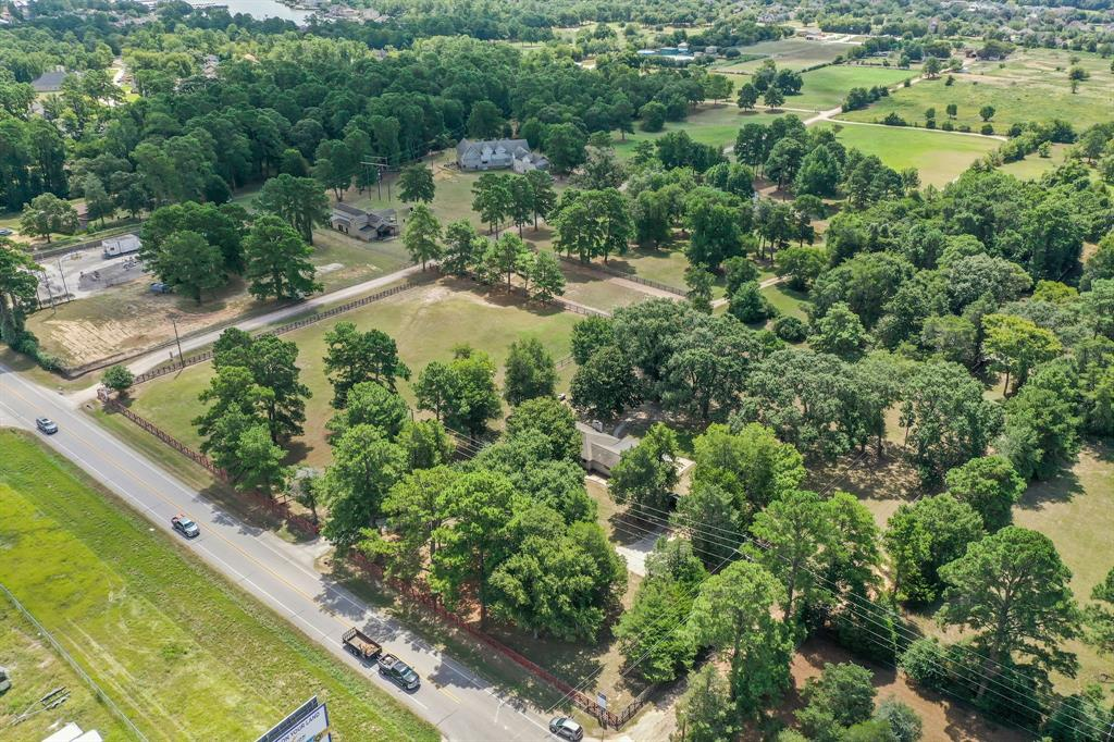 """The property is unrestricted, boasts over 436 feet of fast-developing and highly visible FM 1097 road frontage, and is prime land for various buyers/investors. It is centrally located between I-45 and State Hwy 149, 1/2 mile west of the Rotary Friendship Bridge over Lake Conroe. This picturesque property is groomed and manicured, perfect for a residence, business, or a combination of the two. The house sells """"as-is,"""" offers 1751 square feet of space, is currently livable, and can easily be converted into office space. The widening of FM 1097 east of this property and the proximity to Lake Conroe makes this an excellent investment opportunity with promising growth. Contiguous 16+ acres are also available for purchase."""