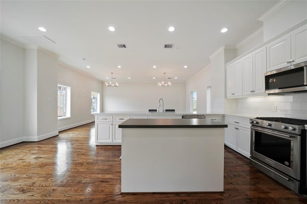 Kitchen also includes stainless steel appliances, a gas range, and built-in microwave.
