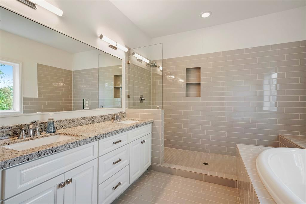 The primary bathroom offers double sinks with granite counter-tops, a spacious garden tub, and large separate shower.