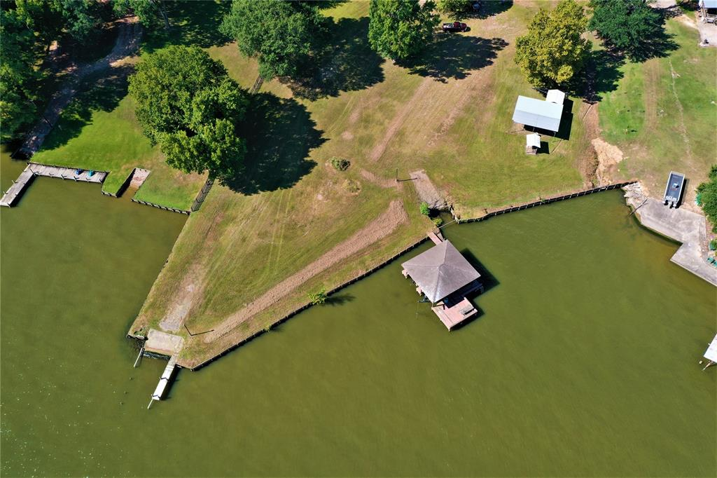 HUGE LAKE LIVINGSTON LAKEFRONT INVESTMENT OPPORTUNITY!!! 17.63 Acres of UNRESTRICTED property with approximately 415 ft of lake frontage. Private boat launch, pier, Boat house with slips, 1872 sq ft home, 22X24 ft metal workshop on slab, personal well and community water, fenced back yard and recently surveyed. This property is situated on the best part of the lake, looking right across the channel at the highly desired Cape Royale Subdivision and right around the lake corner from Wolf Creek Park, where boats can pull up and fill up with gas. Just a short distance from the main body of water, where you'll find the best skiing, tubing and the infamous Pine Island. Great fishing!! Place rental cabins on either side coming into the property for additional income. WHY NOT DREAM BIG AND BUILD A CONDO ON THE LAKEFRONT?? Or just use this as your private getaway like the current owner has for the past 50 years! Do with it what you want. REMEMBER!! UNRESTRICTED!!!! Call for exclusive showings!
