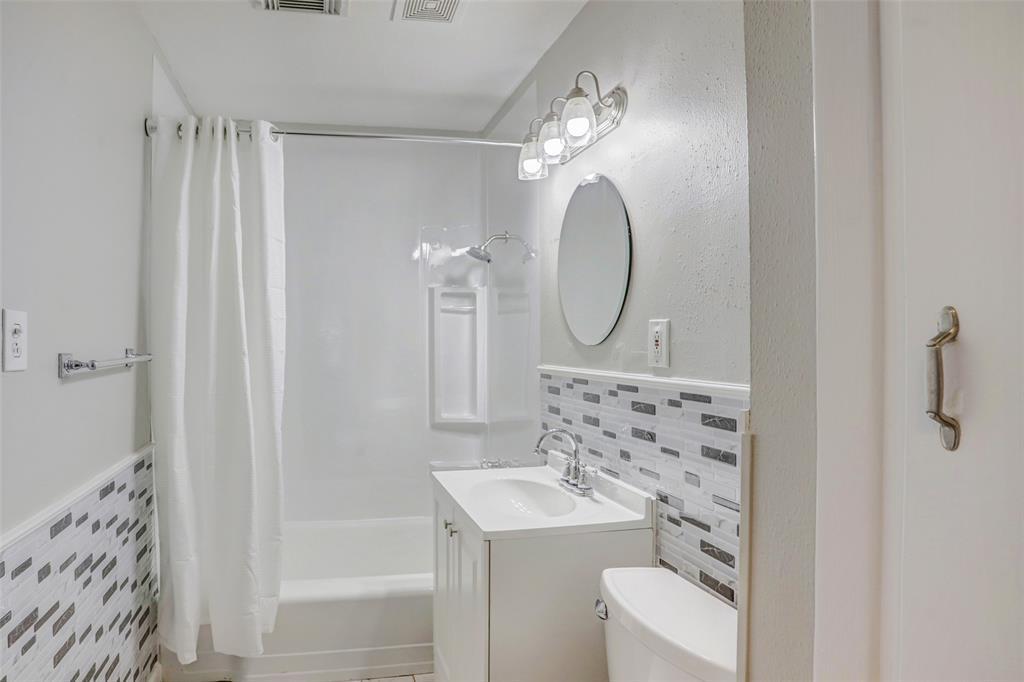 White, bright bathroom off the hallway.