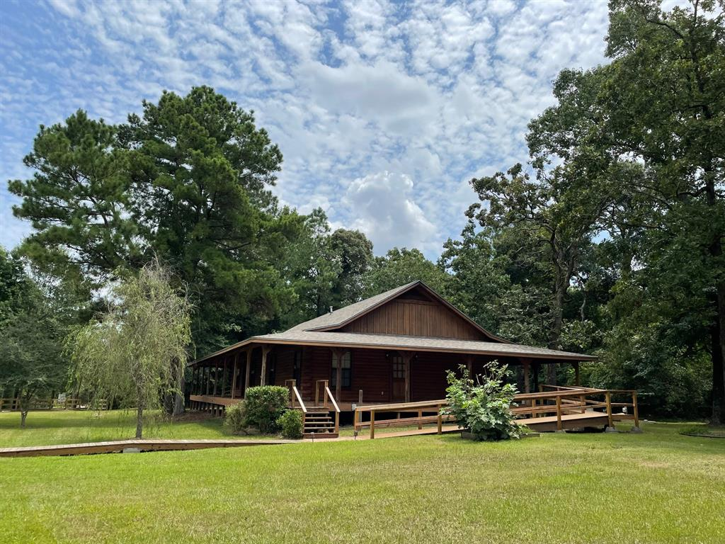 """Just over 3 Acres, unrestricted with no HOA maintenance fees or MUD taxes, lovely log home designed for happy practical living. New roof in 2018, on home & original section of 6,300 SF metal bldg.= plenty of room for storing cars, trucks, workshop, etc. or rent out. Room aplenty for garden, chickens, pets, games and fun.  New ovens and Smartcore waterproof Vinyl planks in Kitchen & Baths.  Wood floors are solid oak planks. Blinds on most windows. Open attic is a """"model"""" for how to make the whole attic useable. If you can climb a ladder see it!  On this wrap around porch you can have a section for each: relaxing outside & enjoying nature, planter garden, chidren's play area, & a BBQ grill outside the Breakfast room!  Ideally located between 2 highways: 1 mi. to new Aggie Hwy 249 & 1mi. to 1774. Designed to enjoy & call """"home"""" whatever your age!  Note: 2 tax IDs are being combined; shop tax info was not included in program figures."""