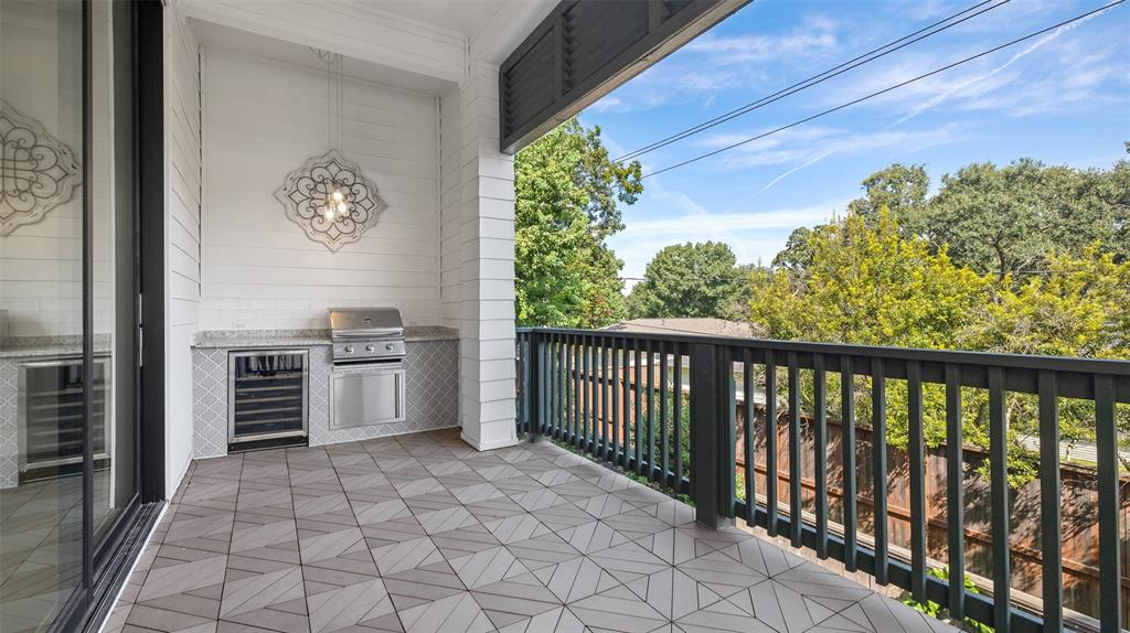 You are going to absolutely love this large balcony with a built-in outdoor kitchen.  The balcony overlooks the one story homes in Timbergrove, which is dotted with mature trees. The outdoor kitchen includes granite countertops, a gas grill, and a wine fridge.