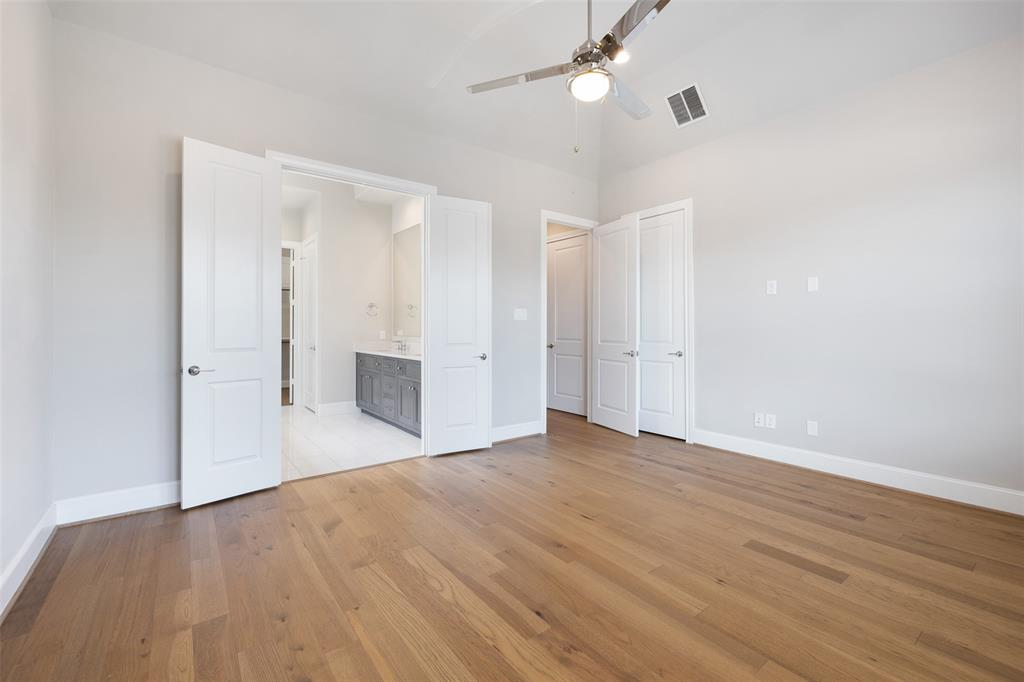 This king-sized primary bedroom includes wood floors, ceiling fan, 2 primary closets, and great views of the adjoining neighborhood.