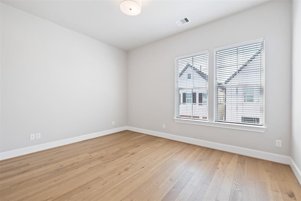 On the same floor as the primary bedroom, you will find this secondary bedroom. This room, like all of the rooms in this home, includes wood floors. Unlike some area new construction, this home already has window blinds installed throughout.
