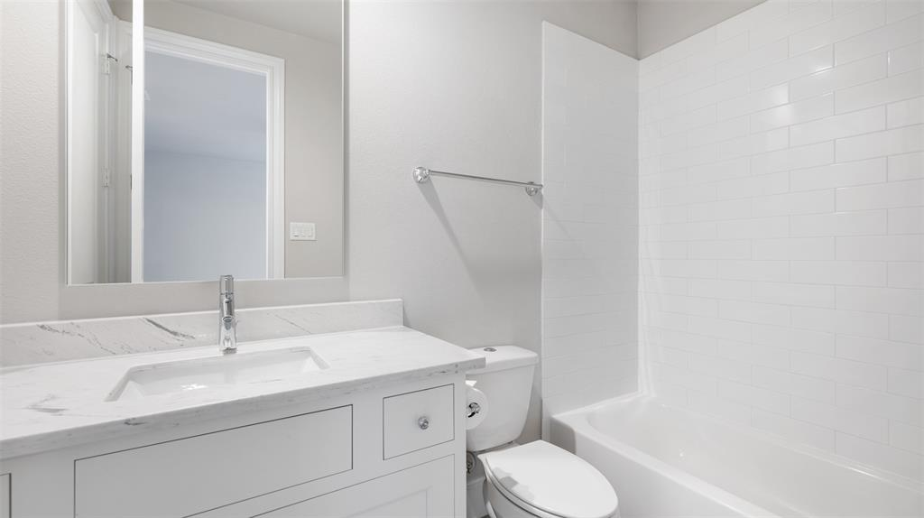 This en suite bathroom is located immediately off of the downstairs bedroom. It includes gorgeous countertops and a subway tile shower surround.