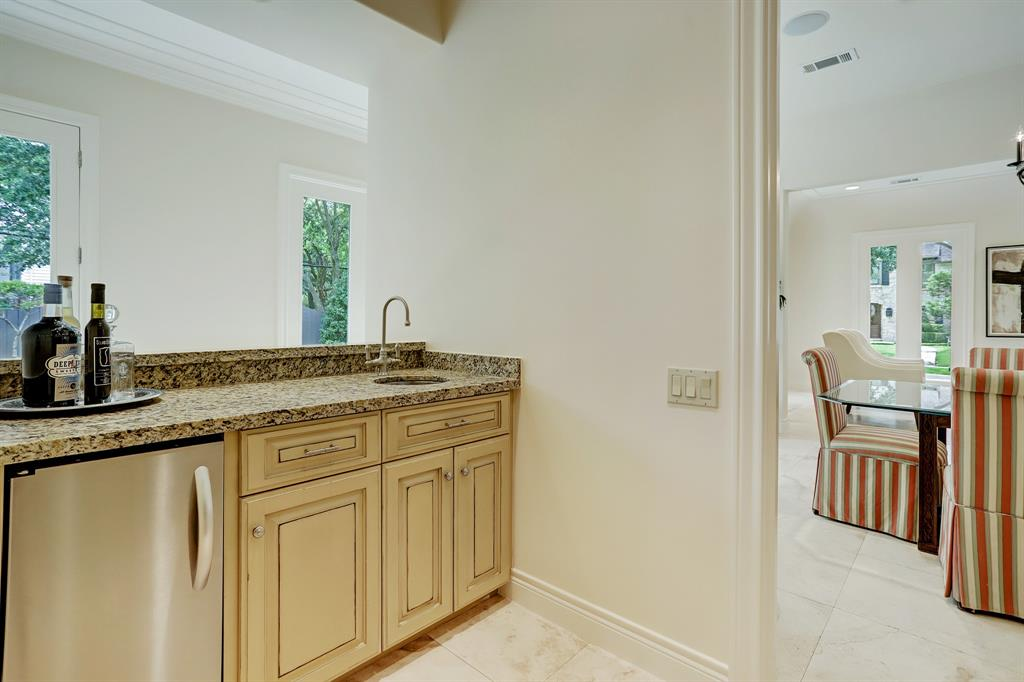 The den is off the kitchen with stylish built-in storage and custom cast stone fireplace.