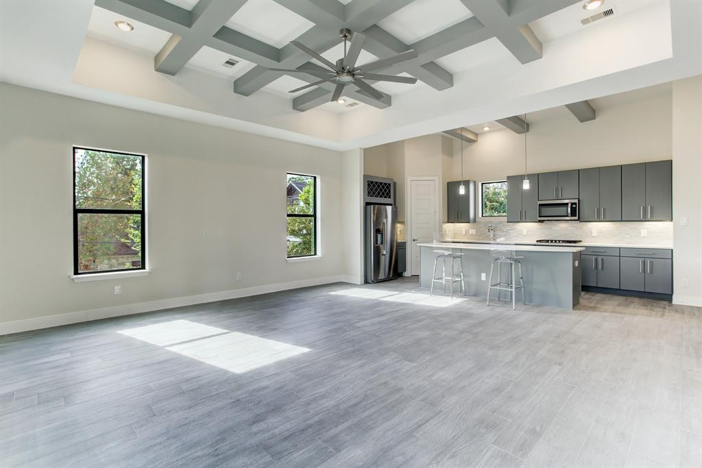 Living room that flows into dinning room with coffered ceilings
